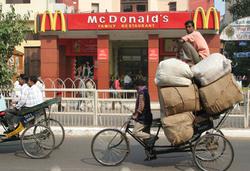Cuando las cadenas de comida rápida como McDonald's se insertaron en los nuevos mercados del Sur, también lo hicieron sus abastecedores globales. Los abastecedores principales de McDonald's a nivel global, Schreiber Foods y Eerie Foods, entraron en India a finales de los noventa y desarrollaron una base de abastecimiento regional para el restaurante. A petición de McDonald's, las compañías se asociaron con la acaudalada familia Goenka y establecieron una enorme compañía procesadora en Maharashtra, que ahora se llama Schreiber-Dynamix. La compañía comenzó por establecer un contrato de producción y centros de recolección para comprar leche de los productores locales, pero luego comenzó a construir su propia granja de gran escala para cubrir sus necesidades. En noviembre de 2010, la compañía inauguró una granja de tecnología moderna con 6 mil vacas en 300 acres del distrito de Pune, apoyados por fondos del State Bank of India. Dynamix también abastece a Danone, Nestlé, Yum! y a KFC. (Foto: USC).