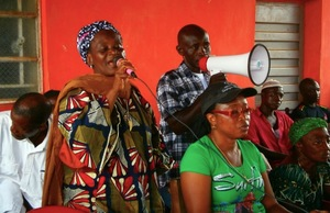 Safiya Vandi (in green t-shirt), pictured at a meeting of communities affected by monoculture plantations in Calabar, Nigeria. When bulldozers came to clear her land, Vandi stood in front of them. (Photo: GRAIN)